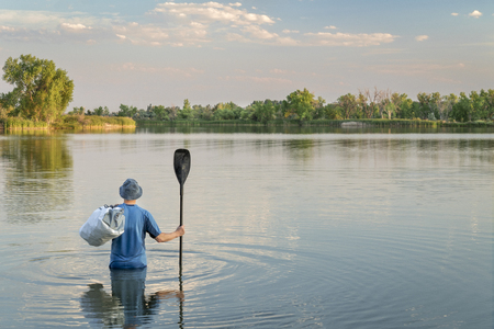 a man with a paddle and waterproof duffel standing waist deep in water, no boat or paddleboard around Stock Photo