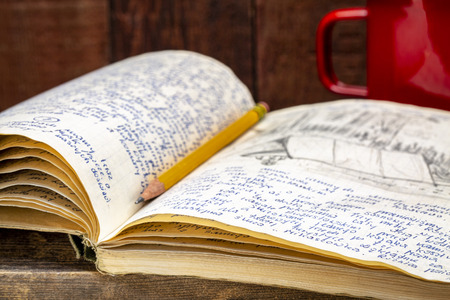 Vintage expedition journal with a metal cup of hot tea on a rustic wood table  - handwriting and drawing in pencil from a kayak trip in Poland in summer of 1974. Stock Photo