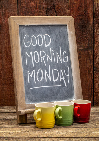 Good Morning Monday sign - white chalk handwriting on a blackboard with cups of espresso coffee against rustic barn wood