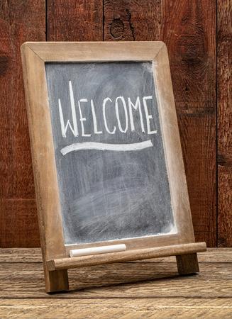 Welcome sign - white chalk handwriting on a blackboard against rustic barn wood