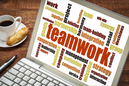 teamwork word cloud on a laptop with a cup of coffee