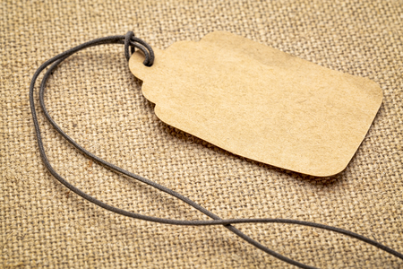 blank paper price tag against burlap canvas - shopping concept