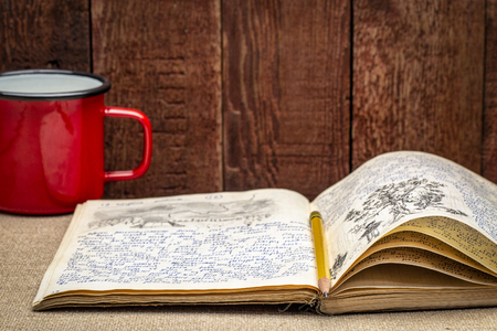 Vintage expedition journal with a metal cup of hot tea - handwriting and drawing in pencil from a kayak trip in Poland in summer of 1974.