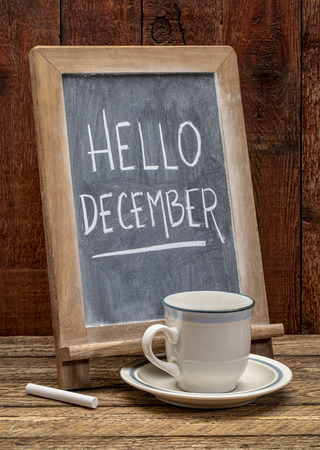 Hello December sign - white chalk handwriting on a blackboard with a cup of coffee against rustic barn wood