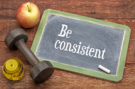Be consistent concept -  slate blackboard sign against weathered red painted barn wood with a dumbbell, apple and tape measure