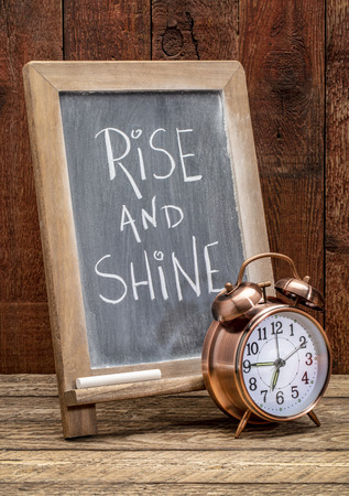 Rise and shine  sign - white chalk handwriting on a blackboard  with an alarm clock against rustic barn wood Stock Photo