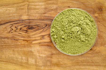 moringa leaf powder in around bowl against olivetree wooden board Stock Photo