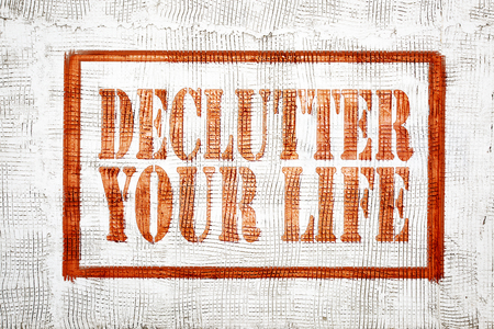 declutter your life - graffiti style sign on stucco wall