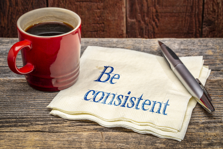 Be consistent concept - handwriting on a napkin with a cup of coffee