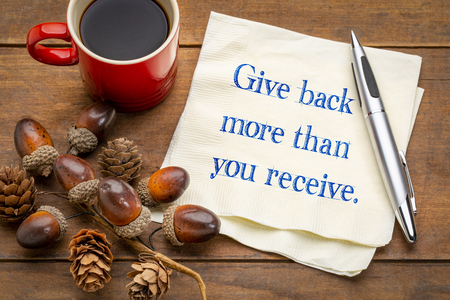 Give back more than you receive - inspirational handwriting on a napkin with a cup of coffee
