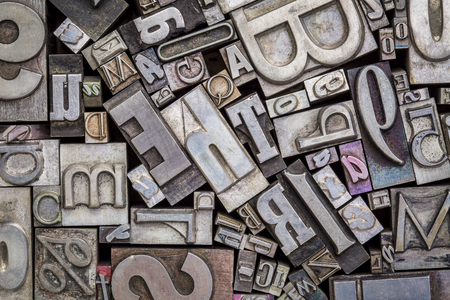 background of random vintage letterpress metal type printing blocks Stock Photo