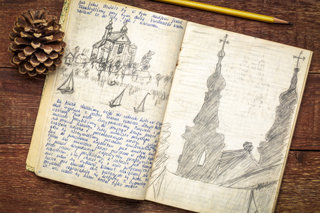 Vintage expedition journal on a rustic wood table  - handwriting and drawing in pencil from a kayak trip in Poland in summer of 1974.