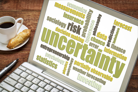 uncertainty and risk word cloud on a laptop with a cup of coffee