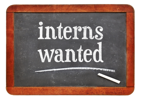 Interns wanted  sign - white chalk text on a vintage slate blackboard