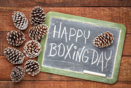 Happy Boxing Day - white chalk handwriting on a slate blackboard with frosty pine cones against rustic barn wood Stock Photo