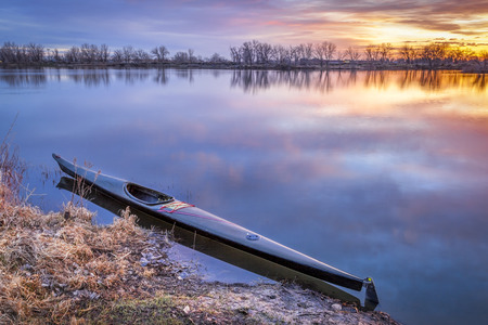 a slim sea racing kayak ready for paddling workout before sunrise on a calm lake in northern Colorado, fall scenery
