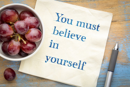 You must believe in yourself - handwriting on a napkin with grapes