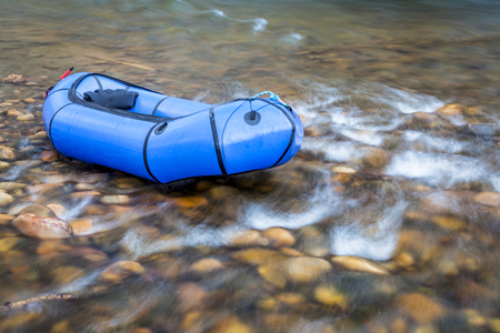 a blue pacraft (one-person light raft used for expedition or adventure racing) on a shallow, rocky t a shallow river Stock fotó
