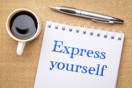 Express yourself inspiraitonal  handwriting in a sketchbook with a cup of coffee