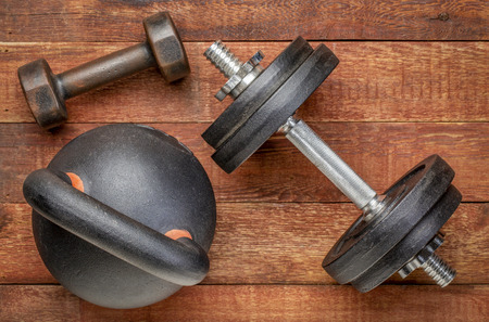 heavy iron kettlebell and dumbbells on a rustic wood background - fitness concept Stock Photo