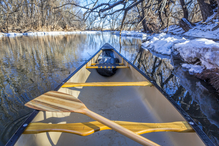 view from a canoe paddling on a river in winter scenery Stock Photo
