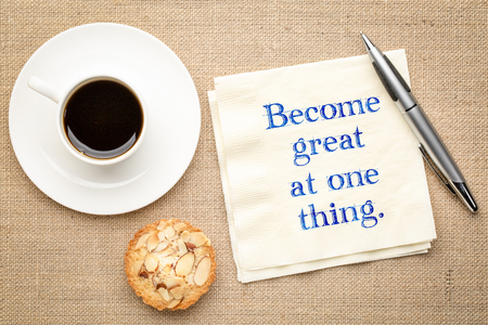 Become great at one thing - inspirational handwriting on a napkin with a cup of coffee
