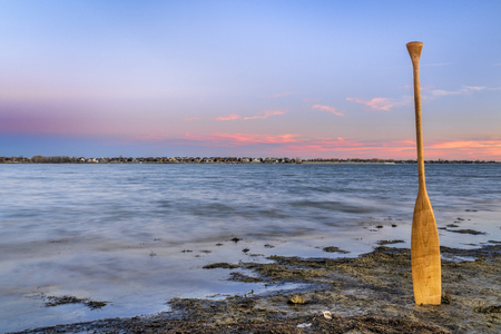 canoe paddle on a lake shore at dusk