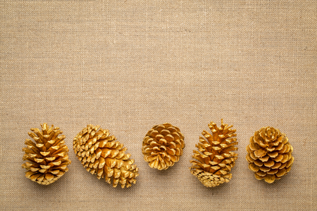 row of decorative, gold  painted, pine cones on a burlap canvas with a copy space Stock Photo
