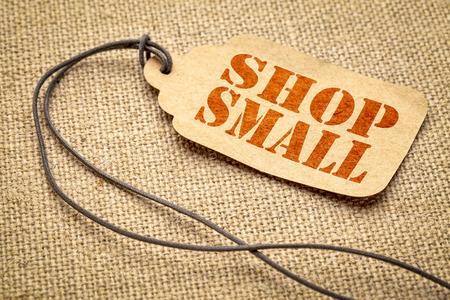 Shop Small - Small Business Saturday concept - a paper price tag with a twine against burlap canvas Stock fotó