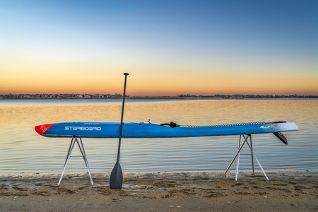 Loveland, CO, USA - November 20, 1918: Dusk over a lake after paddling - a racing stand up paddleboard by Starboard on stands with a paddle.