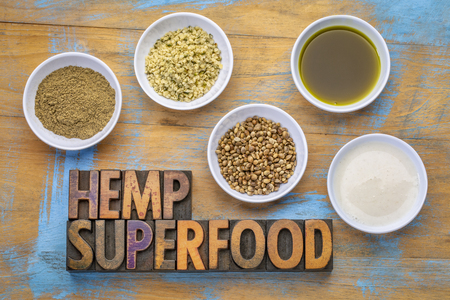 collection of hemp seed products: hearts, protein powder, milk and oil in small white bowls with a text in vintage letterpress wood type