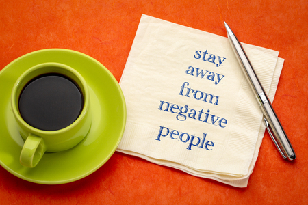 stay away from negative people - handwriting on a napkin with a cup of coffee