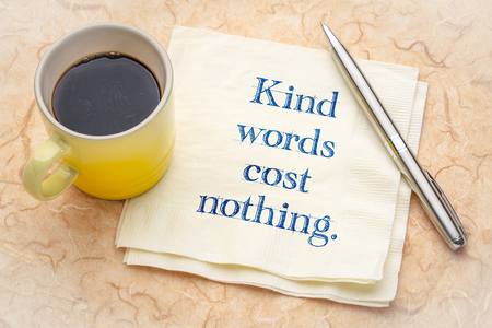 Kind words cost nothing - handwriting on a napkin with a cup of espresso coffee Banco de Imagens