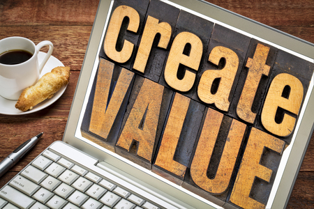create value typography - inspiration concept - words in vintage letterpress wood type blocks on a laptop screen