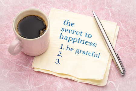 the secret to happiness concept - handwriting on a napkin with a cup of espresso coffee