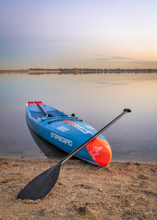 Loveland, CO, USA - November 26, 1918: Dusk over a lake after paddling - a racing stand up paddleboard by Starboard with a paddle and safety leash on a beach.