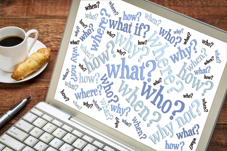 who, what, when, where, why, how questions - brainstorming concept  - word cloud on a laptop screen with a cup of coffee