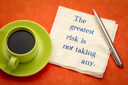 The greatest risk is not taking any - handwriting on a napkin with a cup of coffee Foto de archivo