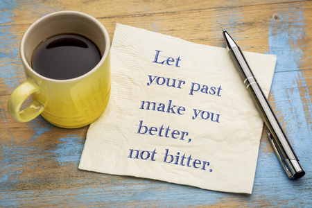 Let your past make you better, not bitter - handwriting on a napkin with a cup of espresso coffee
