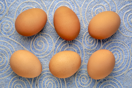 brown chicken eggs, top view on Japanese paper with a spiral pattern