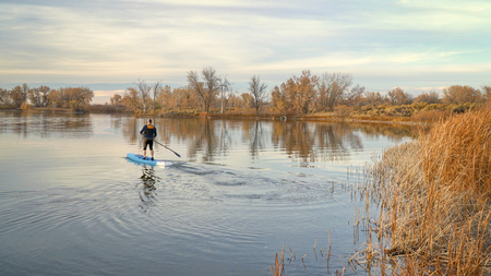 Male paddler is paddling a racing stand up paddleboard on  a calm lake in late fall scenery. Stok Fotoğraf