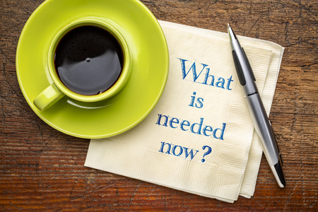 What is needed now? Hnadwriting on a napkin with a cup of coffee.