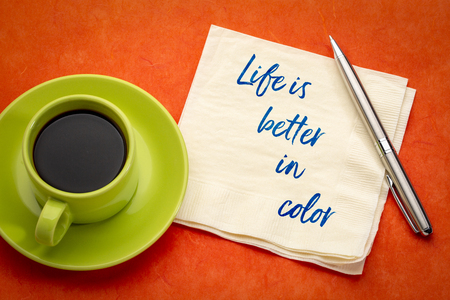 Life is better in color - inspirational handwriting on a napkin againd red mulberry paper with a green cup of coffee Stockfoto