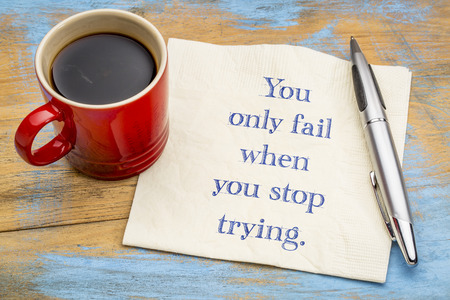 You only fail when you stop trying - handwriting on a napkin with a cup of coffee