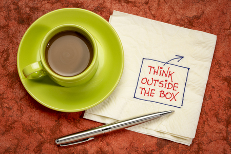 Think outside the box concept - hadwriting on a napkin with a cup of coffee