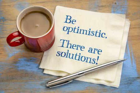 Be optimistic. There are solutions. Inspiraitonal handwriting on napkin with a cup of coffee.