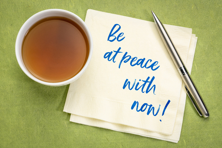 Be at peace with now - inspirational handwriting on a napkin with a cup of tea