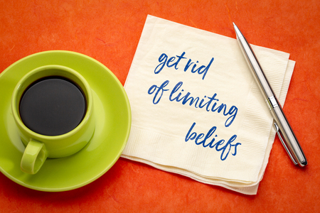 get rid of limiting beliefs - handwriting on a napkin with a cup of coffee Stockfoto