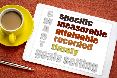 SMART (specific, measurable, attainable recorded, timely) goal setting concept  on a digital tablet with  a cup of coffee