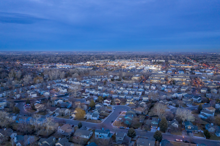 dusk over city of Fort Collins in northern Colorado, aerial view towards plains Фото со стока